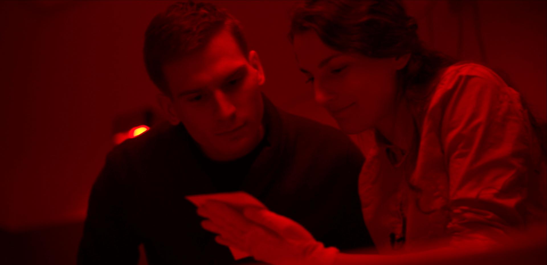 """Dwoje młodych ludzi ogląda zdjęcie w ciemni fotograficznej. Kadr z filmu """"Sztafeta"""", Narodowe Centrum Kultury 2018"""