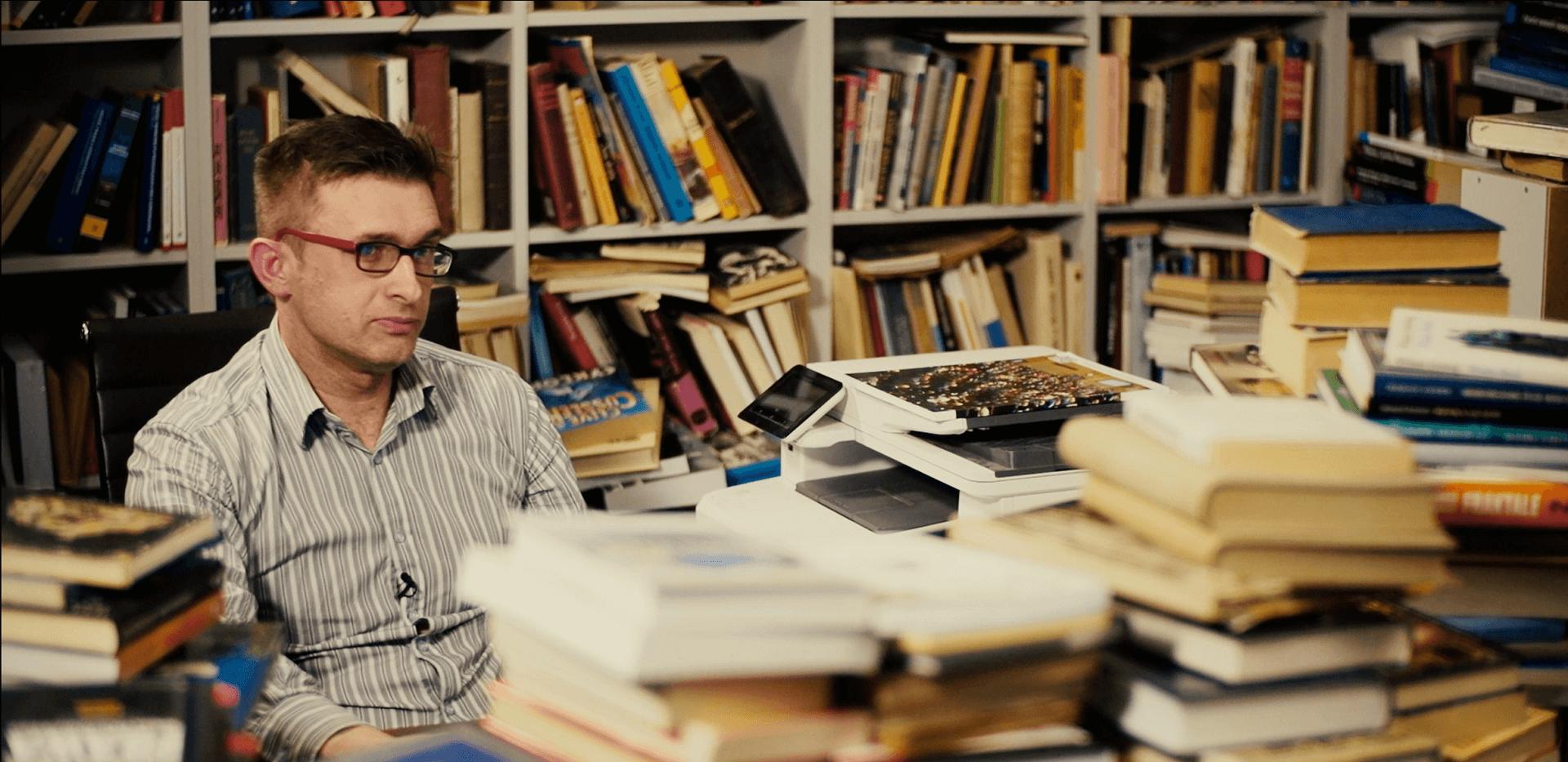 """Sprzedawca w antykwariacie siedzący za blatem pełnym książek. Kadr z filmu """"Sztafeta"""", Narodowe Centrum Kultury 2018"""