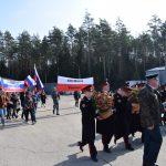 Zdjęcie przedstawiające młodzież zflgami itransparentami wbarwach Polski iRosji - uczestników Marszu Pamięci Młodzieży Polskiej iRosyjskiej stacja Gniezdowo - las katyński.