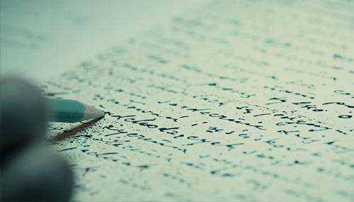 """Zdjęcie naktórymwidać rękę trzymającą ołówek, którywskazuje natrudne doodczytania pismo nakartce papieru. Kadr zfilmu """"Sztafeta"""", Narodowe Centrum Kultury 2018"""