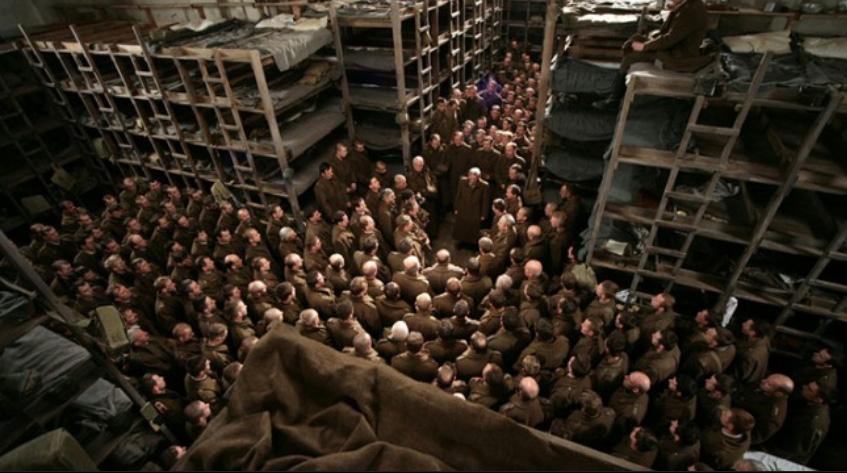 Kadr z filmu Katyń Andrzeja Wajdy z 2007 roku. Duża grupa uwięzionych żołnierzy polskich stoi stłoczona w obozowym baraku. Żołnierze ubrani są w płaszcze oficerskie. Za nimi widać wysokie prycze.