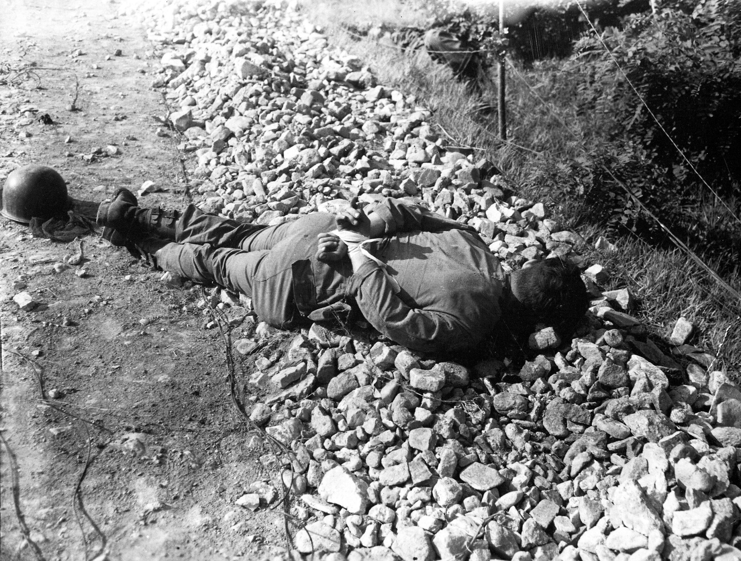 Na zdjęciu martwy amerykański jeniec wojenny leżący zeskrępowanymi rękami, zastrzelony strzałem wtył głowy przezchińskich lub koreańskich komunistów, Korea 1950
