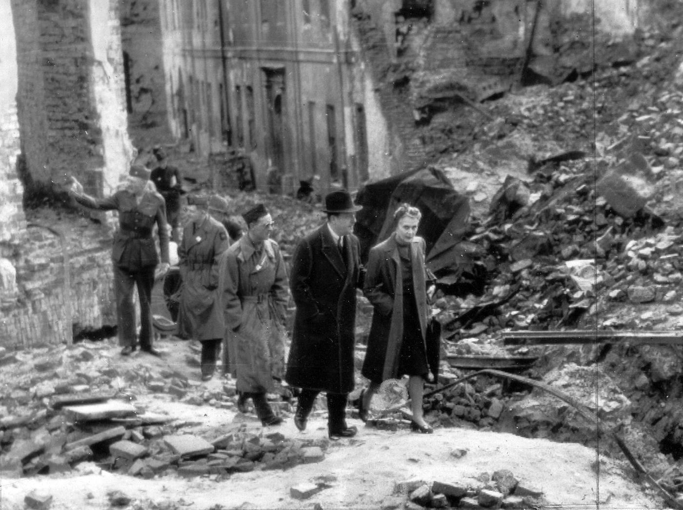 Na zdjęciu Ambasador USA wPolsce, Arthur Bliss Lane wruinach Warszawy, 1945 rok Ambasador idzie podrękę zkobietą, prawdopodobnie żoną pośród ruin miasta. Zanimi grupa kilku żołnierzy amerykańskich.