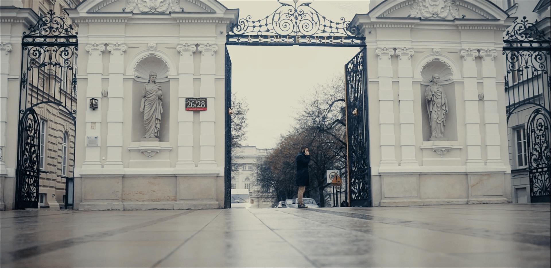 """Młody człowiek stojący przed bramą główną Uniwersytetu Warszawskiego i rozmawiający przez telefon. Kadr z filmu """"Sztafeta"""", Narodowe Centrum Kultury 2018"""
