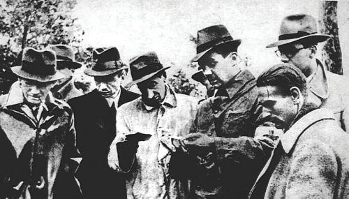 Zdjęcie przedstawiające mężczyzn wkapeluszach, ubranych wpłaszcze przeglądających dokumenty. Są toczłonkowie międzynarodowej delegacji wizytujący miejsce ekshumacji wKatyniu w1943 roku