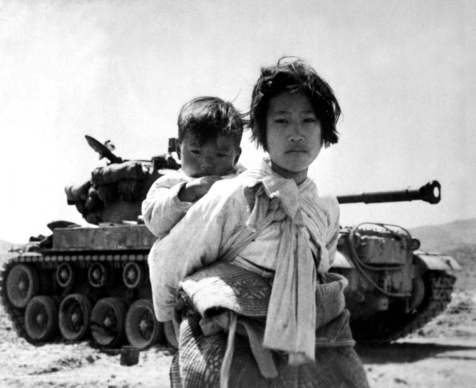 Koreańska dziewczynka z młodszym bratem na plecach, w tle czołg amerykański M-46 Patton, Haengju, Korea, czerwiec 1951. Zdjęcie z domeny publicznej rządu USA